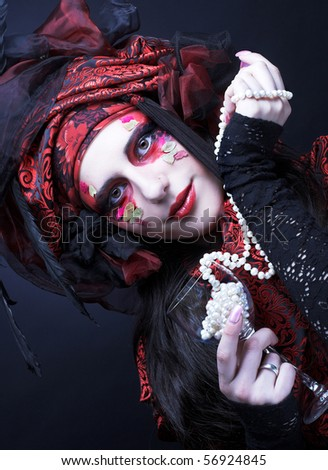 Young lady in turkish style in black and red silk and with beads