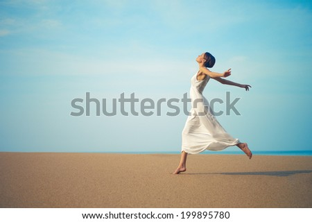 Young lady in white dress jumping on the beach - stock photo