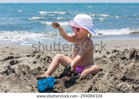 young lady is building a sand castle on the sea shore - stock photo