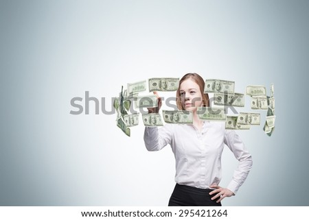 Young lady is controlling cash flow of the dollar notes. Light blue background.n - stock photo