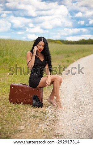young lady is waiting car on village road and talking by mobile phone. She is little angry - stock photo