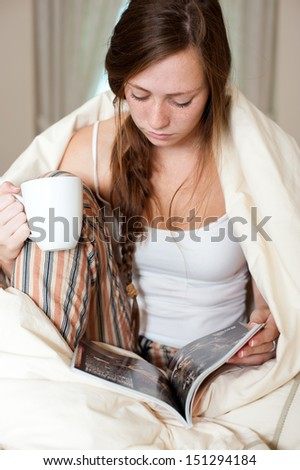 Young lady just woke up sitting in bed checking her laptop computer and having a cup of coffee. - stock photo