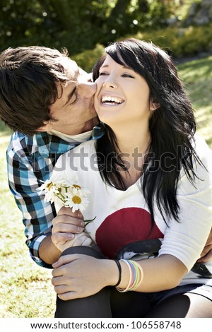 Young lady laughing while young man kisses and gives her flowers - stock photo