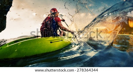 Young lady paddling hard the kayak with lots of splashes - stock photo