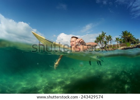 Young lady paddling on the surf board - stock photo