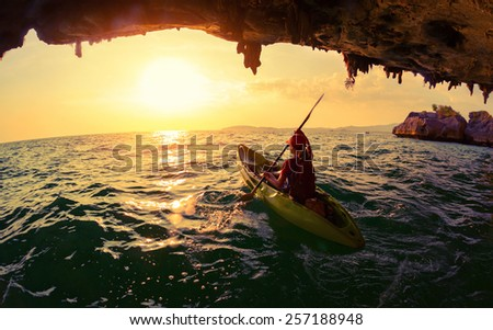 Young lady paddling the kayak from limestone cave towards open sea - stock photo