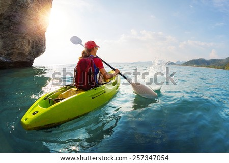 Young lady paddling the kayak near the cliff at sunny day
