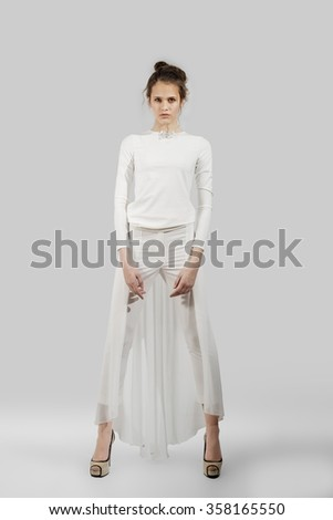young lady posing in long white dress