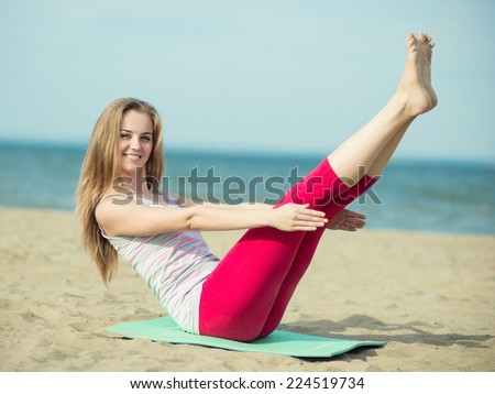 Young lady practicing yoga. Beautiful woman posing at the summer sand beach.  Beautiful fit tan girl. Fitness model caucasian ethnicity outdoors. Weight loss exercise. Meditation. - stock photo