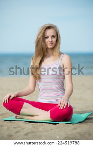 Young lady practicing yoga. Beautiful woman posing at the summer sand beach. Workout near ocean sea coast. Beautiful fit tan girl. ?aucasian ethnicity outdoors. Weight loss exercise. Meditation. - stock photo