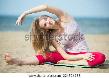 Young lady practicing yoga. Beautiful woman posing at the summer sand beach. Workout near ocean sea coast. Beautiful fit tan girl. Fitness model caucasian ethnicity outdoors. Weight loss exercise.  - stock photo