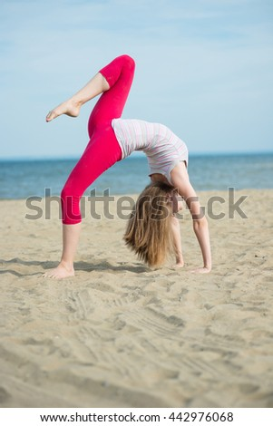 Young lady practicing yoga. Beautiful woman posing at the summer sand beach. Workout near ocean sea coast. Beautiful fit tan girl. Fitness model caucasian ethnicity outdoors. Weight loss exercise