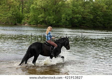 Young lady riding horseback in the river