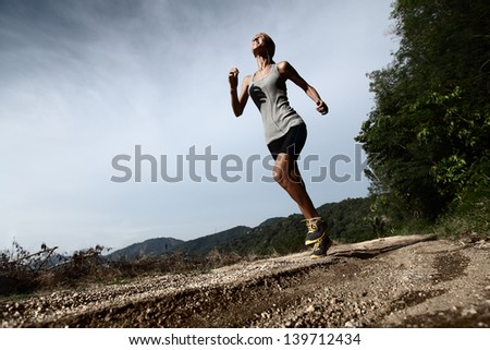 Young lady running along rural road. There is expression of efforts on the face - stock photo