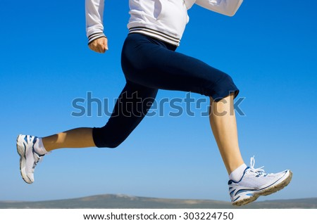 Young lady running. Fitness model outdoors.