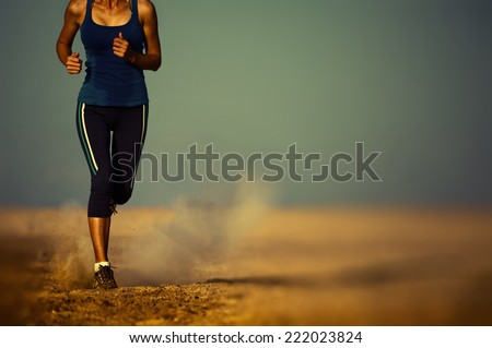 Young lady running in the desert. Edges are blurred focus on the foot - stock photo