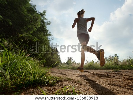 Young lady running on a rural road during sunset - stock photo