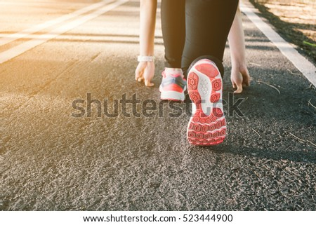 Young lady running on road closeup on shoe., at time sunset.