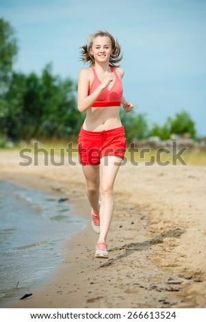 Young lady running. Woman runner running at the sunny summer sand beach. Workout near ocean sea coast. Beautiful fit girl. Fitness model caucasian ethnicity outdoors. Weight loss exercise. Jogging. - stock photo