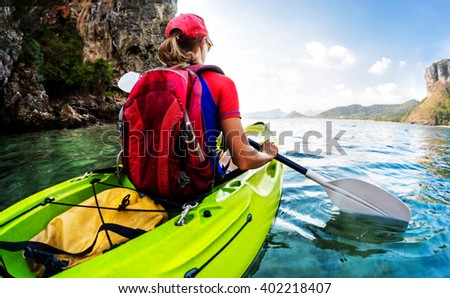 Young lady sits in the kayak with a paddle in the sea