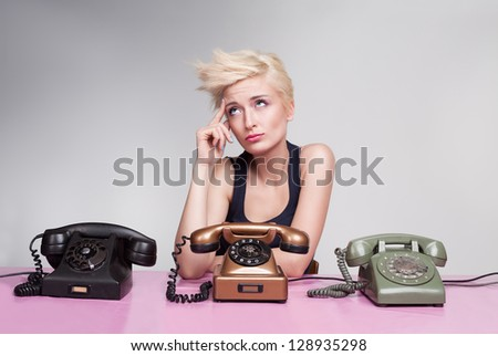 young lady sitting and thinking on a pink desk with colorful antique phones - stock photo