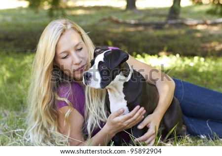 Young lady sitting in the shade with her Pit Bull puppy - stock photo