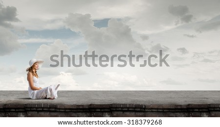 Young lady sitting on building roof with laptop on knees