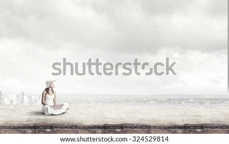 Young lady sitting on building roof with laptop on knees - stock photo