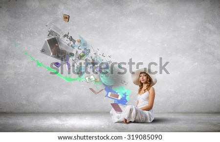 Young lady sitting on floor with laptop on knees - stock photo