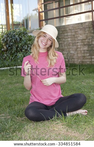 Young lady sitting on garden  - stock photo