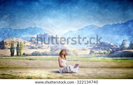 Young lady sitting on grass with laptop on knees - stock photo