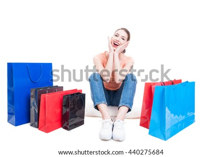 Young lady sitting with shopping bags around and feeling cheerful isolated on white background with advertising area - stock photo