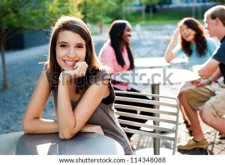 Young lady smiling with friends in the background talking - stock photo