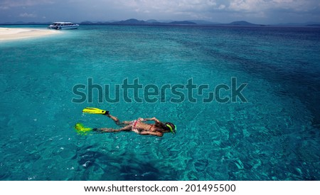 Young lady snorkeling in the clear tropical sea at sunny day - stock photo