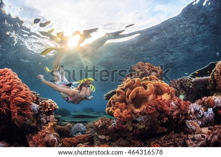 Young lady snorkeling over coral reef in the tropical sea.
