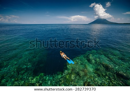 Young lady snorkeling over the reef wall in the area of the island of Bunaken, Sulawesi, Indonesia - stock photo