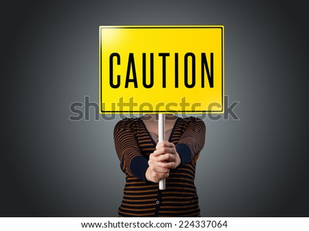 Young lady standing and holding a yellow caution sign in front of her head - stock photo