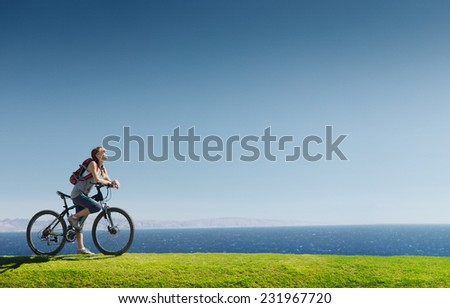 Young lady standing on the green meadow with bicycle