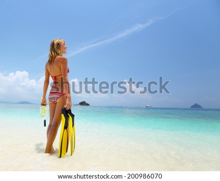 Young lady standing on the tropical sandy beach with snorkeling gear - stock photo