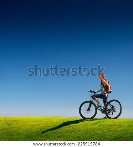 Young lady standing with bicycle on the green lush meadow