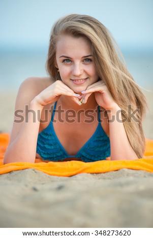 Young lady sunbathing on a beach. Beautiful woman posing at the summer sand beach. Outdoor summer portrait of pretty sport style woman in blue bikini. Ocean sea coast. Beautiful fit tan girl. Sexy - stock photo