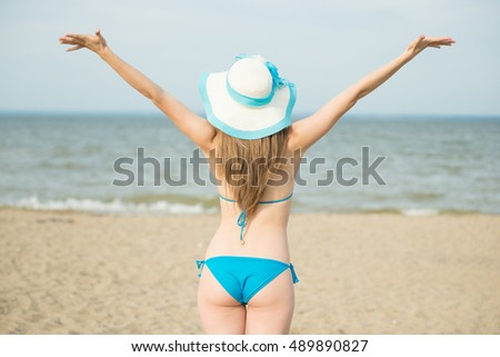 Young lady sunbathing on a beach. Beautiful woman posing at the summer sand beach. Outdoor summer portrait of pretty sport style woman in blue bikini. Ocean sea coast. Beautiful fit tan girl. Sexy