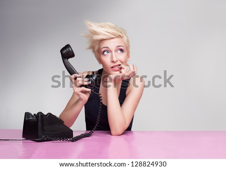 young lady thinking with her finger in her mouth and holding handset of antique phone - stock photo