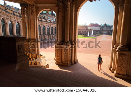 Young lady tourist walking in a yard among old building (Zwinger) in Dresden - stock photo