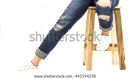 Young lady wearing fashionable jean sitting on a chair isolated on white background