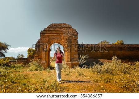 Young lady with a backpack out of the gates of the ancient ruins.