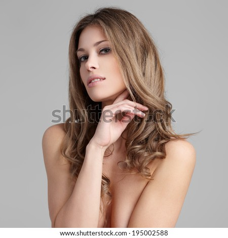 Young lady with a beautiful hair on gray background - stock photo
