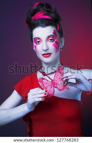 Young lady with artistic make-up and with feathers in her hair and with red butterfly
