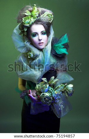 Young lady with artistic visage and with flowers in her hands and hair