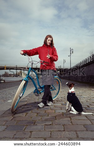 Young lady with bicycle and dog on river bank - stock photo